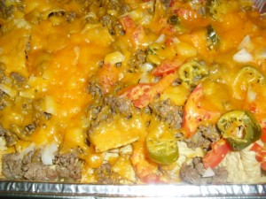Family night nachos with ground beef and cheese, jalapeños, tomatoes, and sour cream.