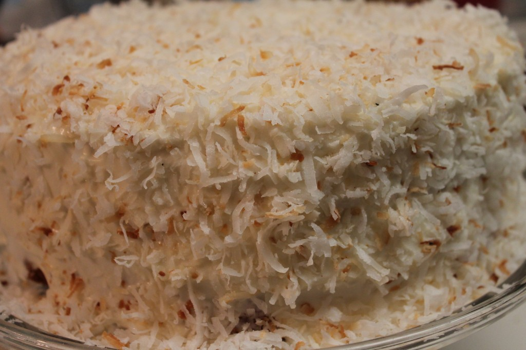 A moist and fluffy cake topped with a sweet whipped frosting and toasted coconut shavings