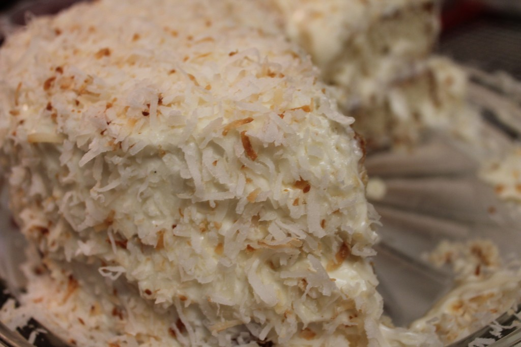 Sweet, moist white cake with a homemade whipped cream icing and shaved toasted coconut flakes
