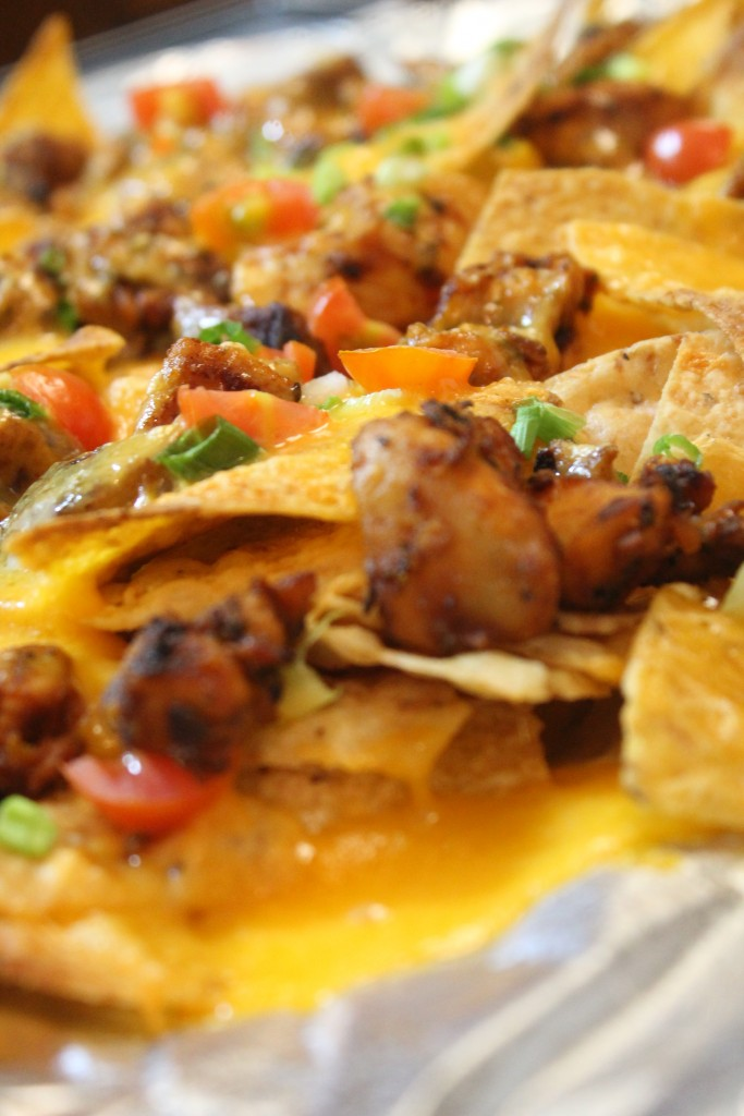 Seasoned grilled chicken, melted cheese and delicious veggies top these game-day nachos.