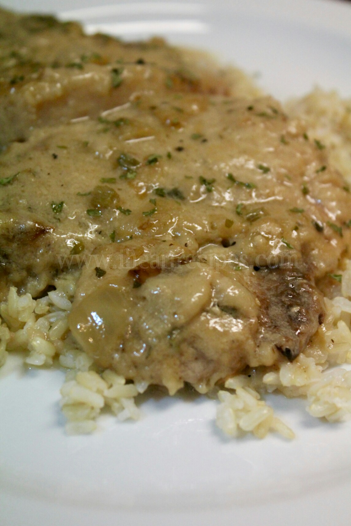 You can serve these amazing smothered pork chops with creamy gravy on a bed of rice with a side of greens!