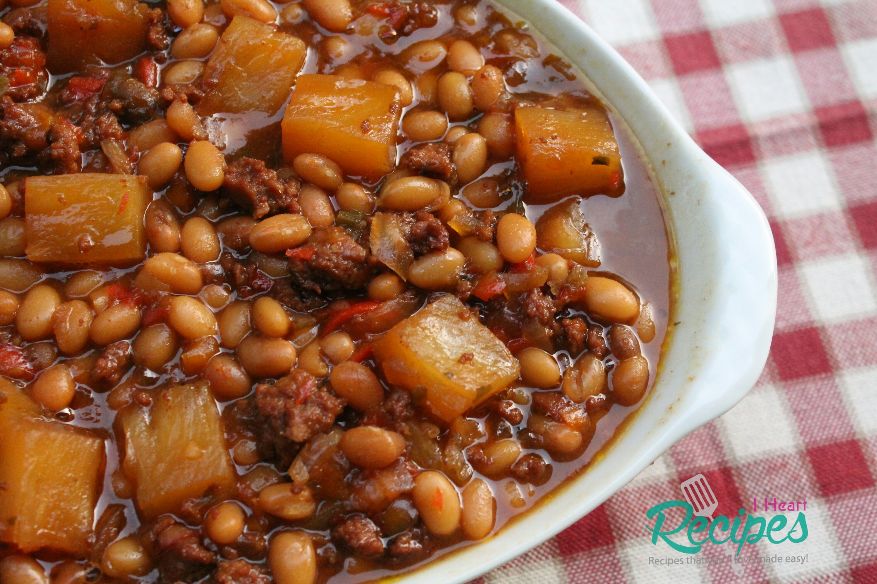 sweet and savory baked beans in a brown sugar sauce with pineapple chunks and bacon