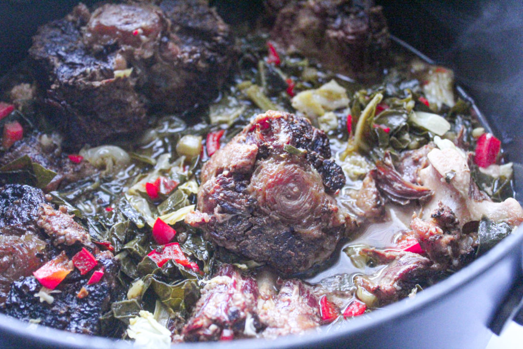 Tender smoked ox tails are cooked with classic collard greens for a delicious southern dish